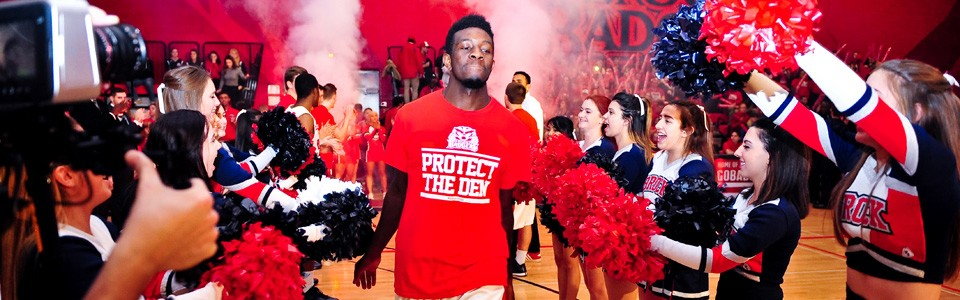 A Brock basketball player enters the court as cheerleaders and the crowd cheer on