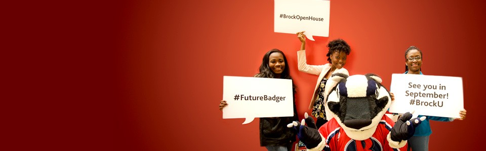 Smiling students posing with Boomer the Badger at Brock's Open House