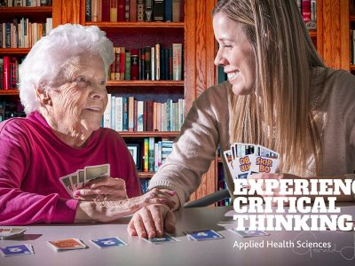 Student playing cards with elderly woman