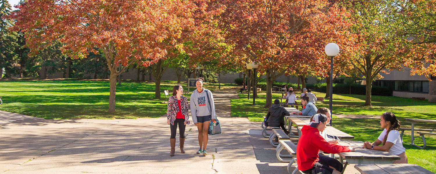 Students walking down a path in Jubilee Court on an autumn day