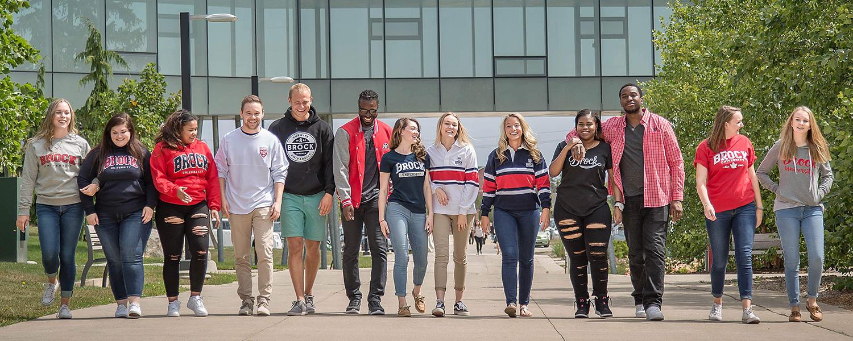 Smiling Brock students walking down the sidewalk
