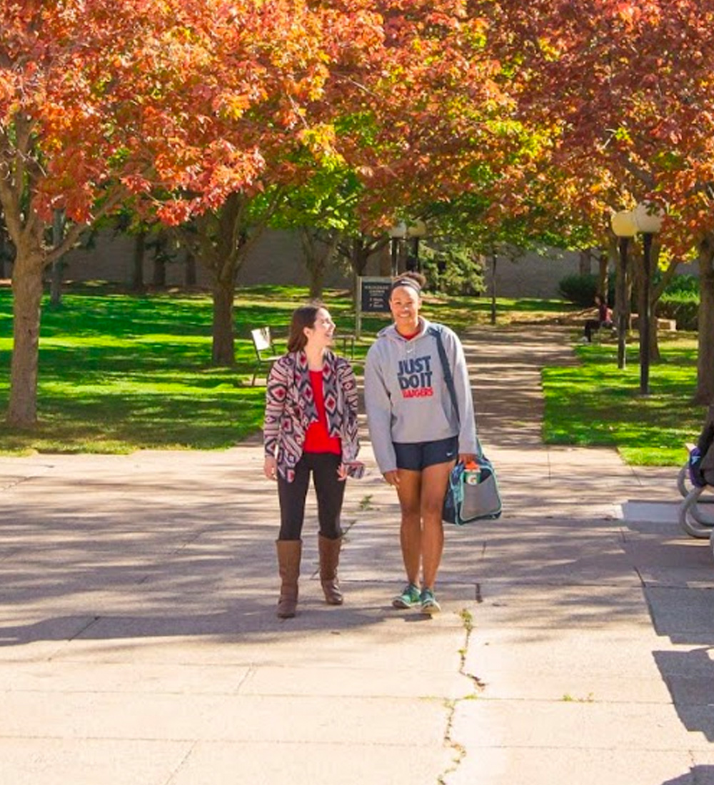Two students walking on campus in the Fall
