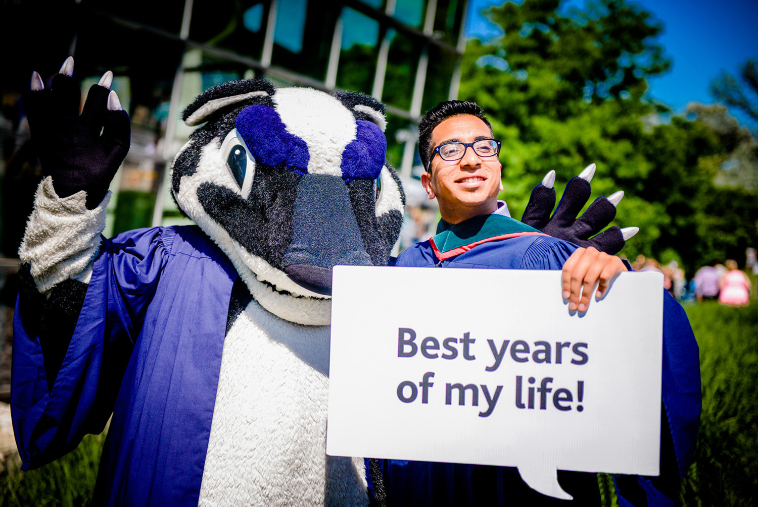 A smiling graduate and Boomer the Badger at Brock University's Convocation