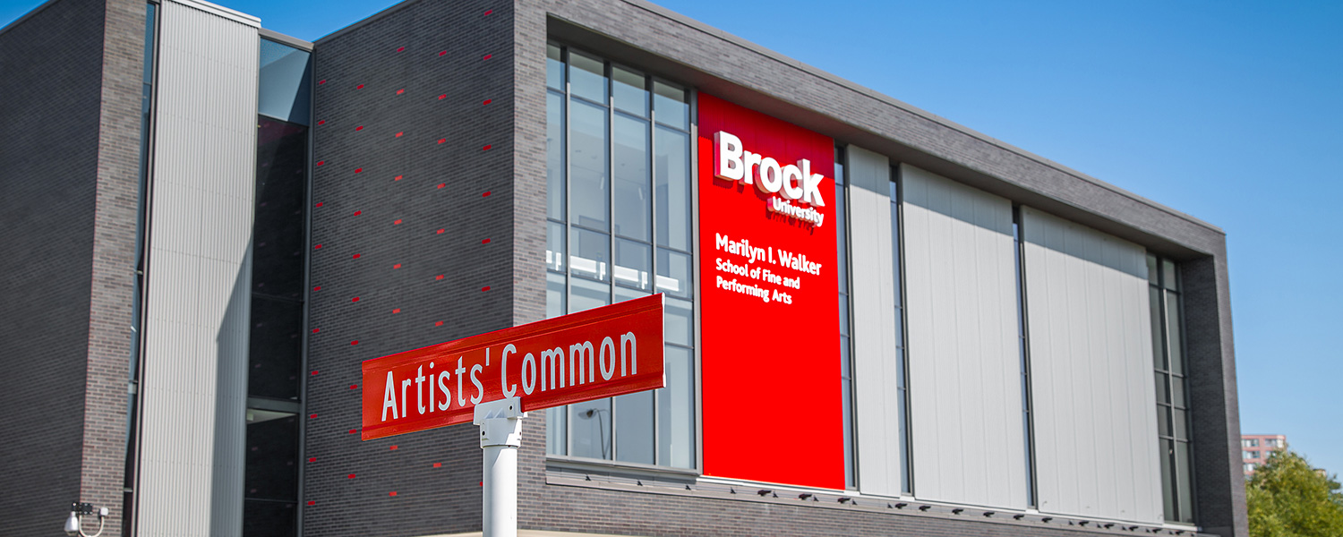 A photo of the front of the Marilyn I. Walker School of Fine and Performing Arts, and the Artists' Common street sign