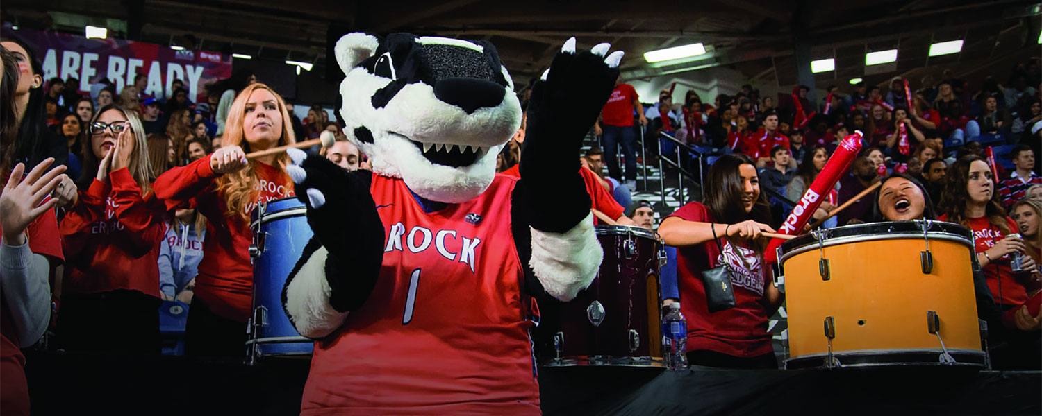 Boomer the Badger cheers for a sports event with students