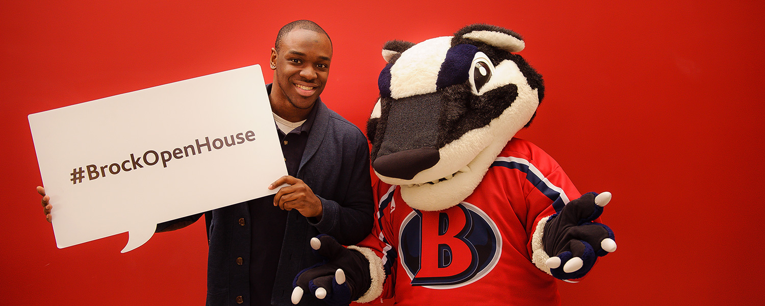 A prospective student posing with Boomer the Badger at Open House