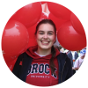 A smiling Brock student surrounded by Brock balloons