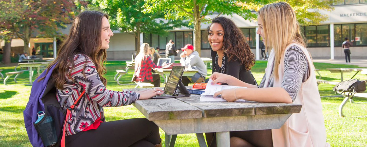brock students sitting at a bench on campus