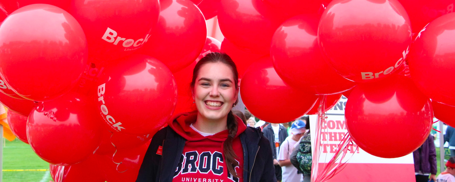 A Brock student holding balloons