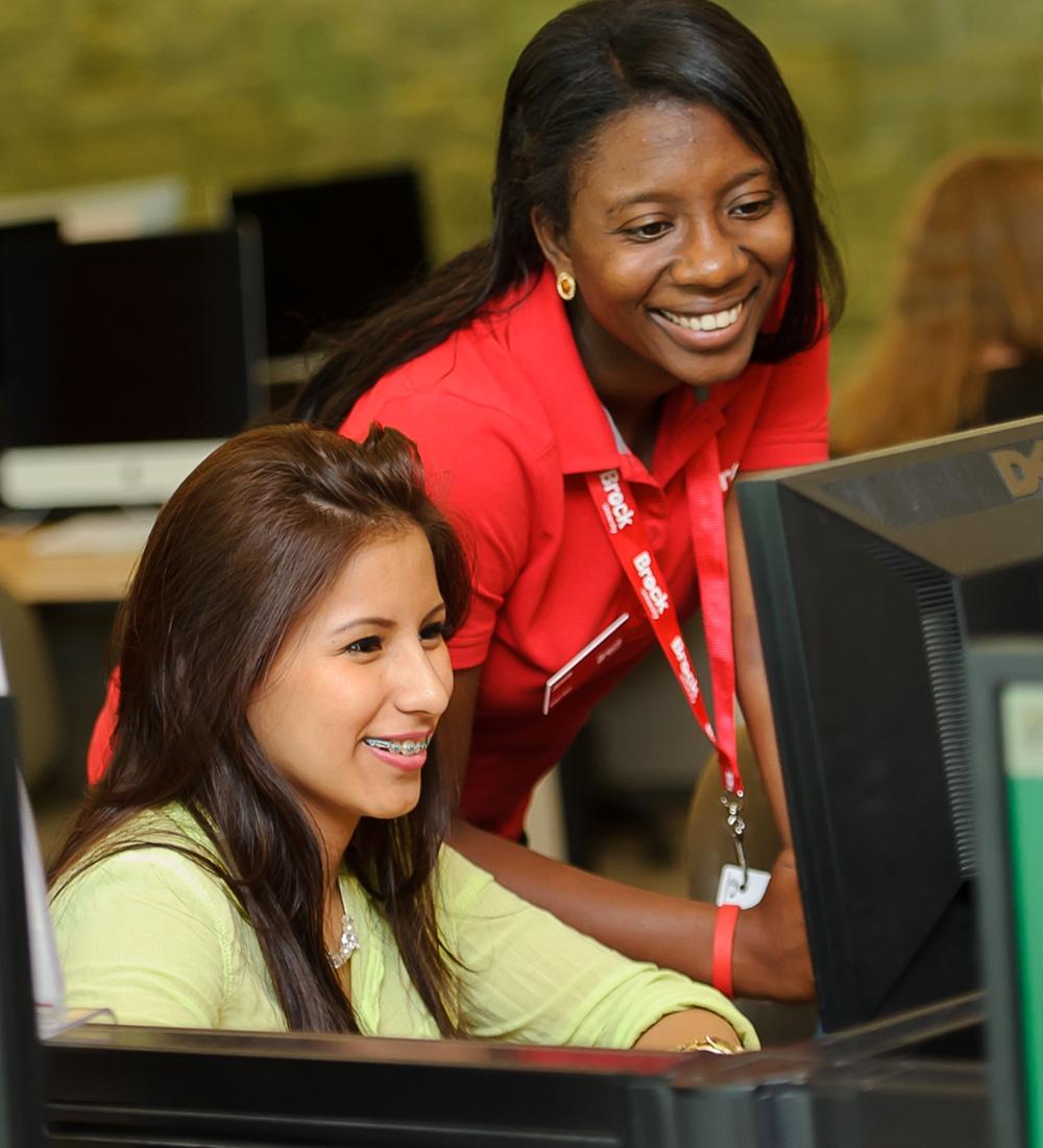 A Smart Start staff member helping a student at a computer.